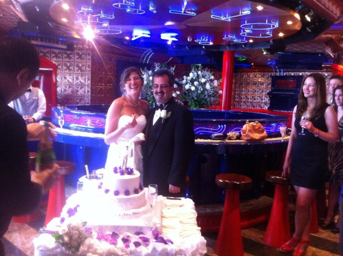 [Image: Happy couple with their cake on the CCL Freedom]